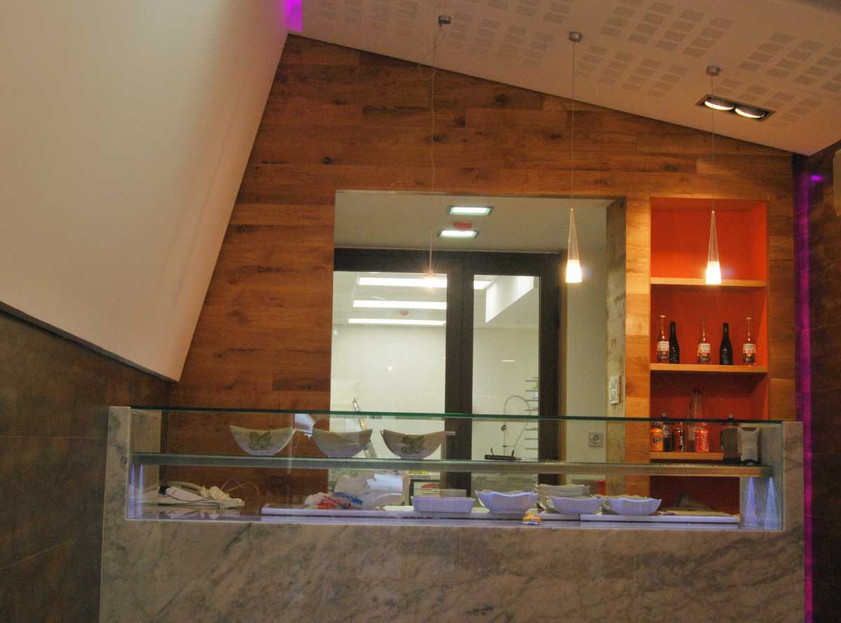 En la zona de venta destaca un gran mostrador-vitrina  de mármol de Carrara, combinado con granito y vidrio, calefactado para la exposición  de los diversos tipos de pizzas.