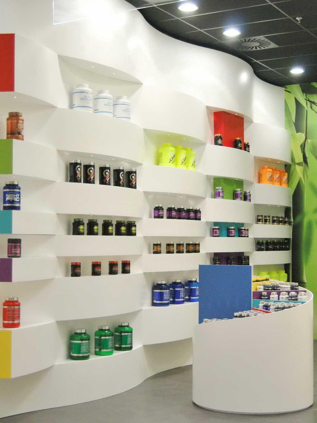 Diseño integral de local comercial para la marca de alimentación deportiva NaturSport. Una gran estantería ondulante cubre la pared de suelo a techo definiendo el espacio.