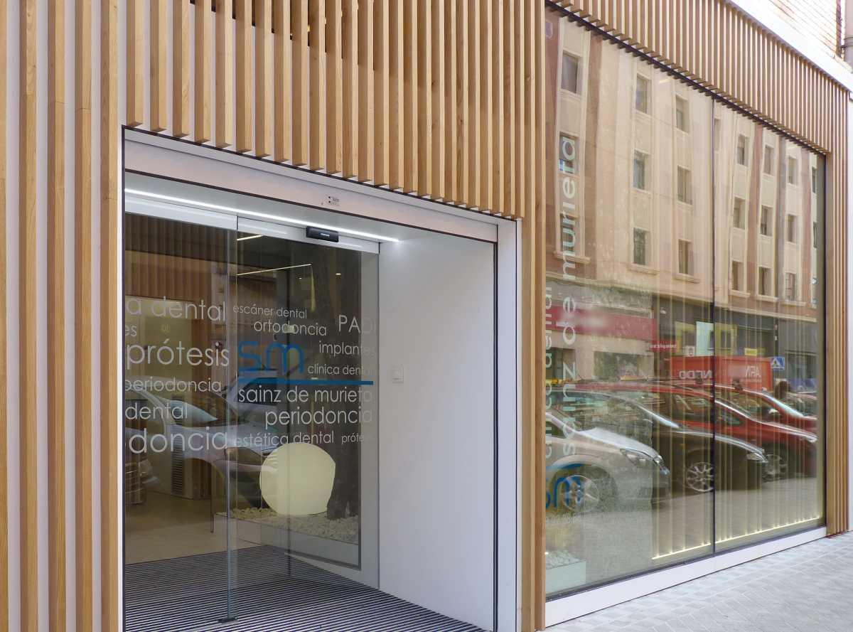 La madera de castaño que amabiliza el ambiente en la zona de espera sale a la fachada para diferenciar y personalizar la imagen exterior
