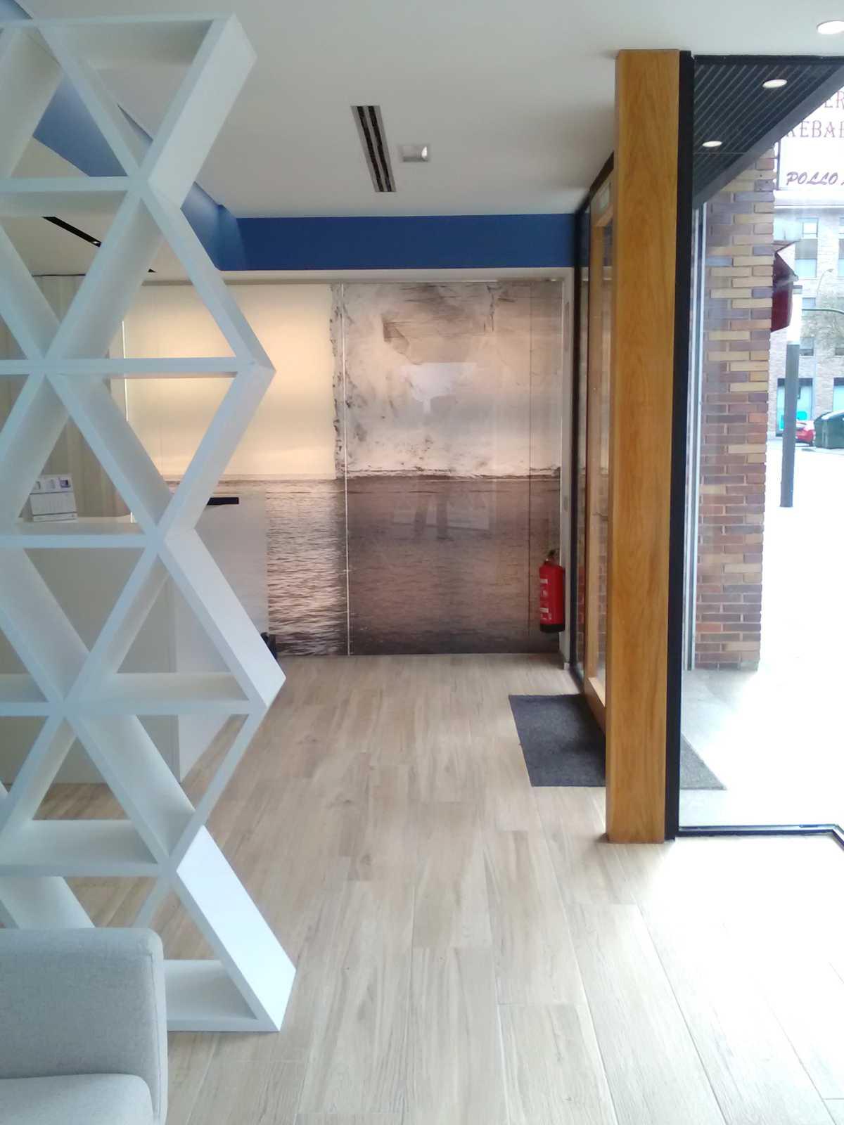 El rediseño de este espacio ha convertido unas oficinas bancarias en una moderna clínica dental. En la recepción, iluminada por la fotografía de un iceberg, una gran estantería enmarca la zona de espera e infantil.