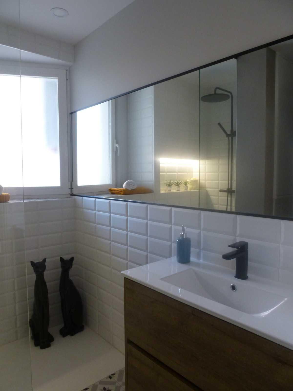 El gran espejo proporciona carácter, luminosidad y profundidad al aseo.